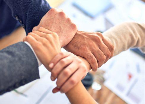 Na obrazku widać splot rąk. każdy trzyma kolejną osobę.
