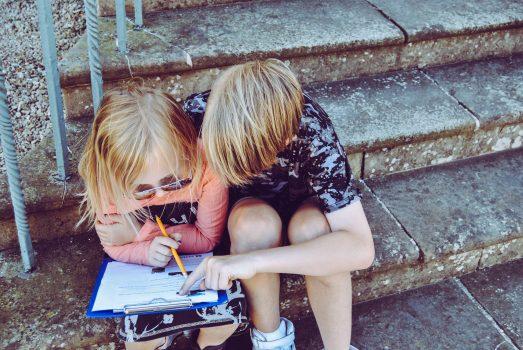 Na zdjęciu widać dwoje dzieci, chłopca i dziewczynkę. Siedzą na kamiennych schodach. Chłopiec pomaga dziewczynce w odrabianiu zadania domowego.